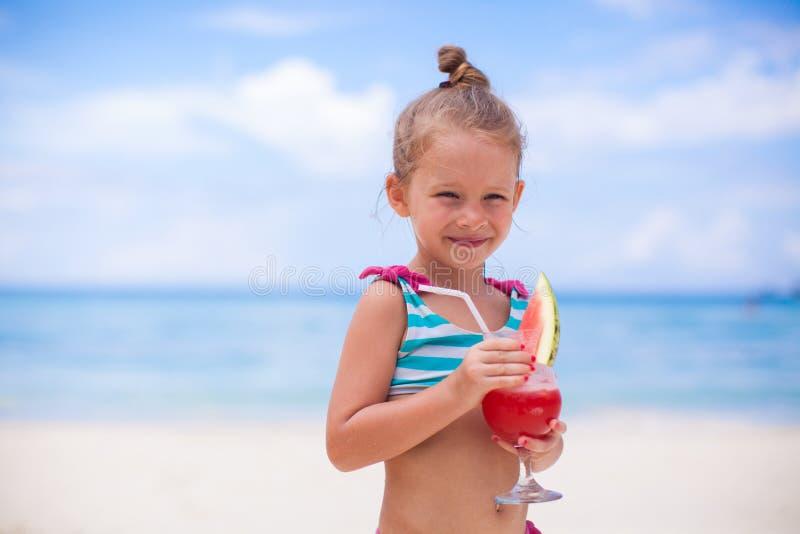 La bambina beve il succo dall'anguria sul fotografia stock