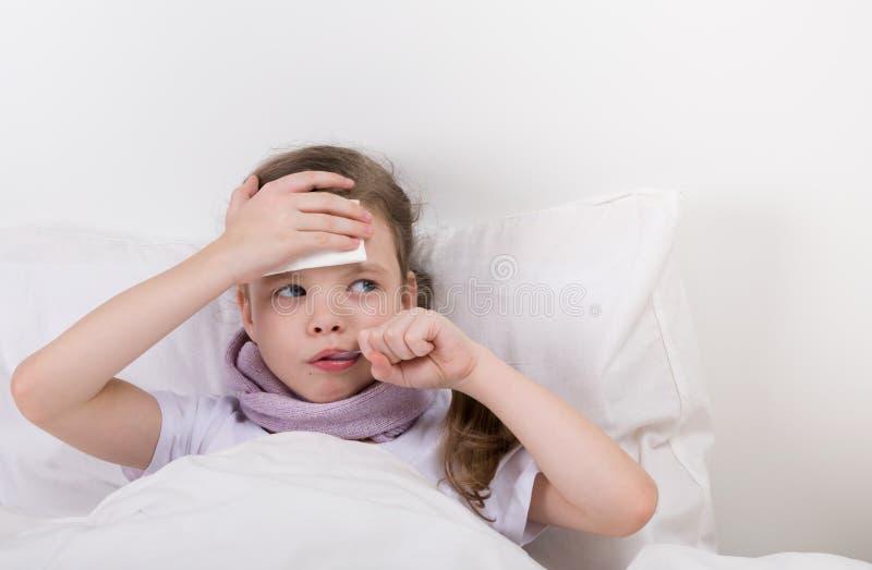 La bambina, bugie a letto e prende la medicina, da un'emicrania ed esamina i diritti immagine stock