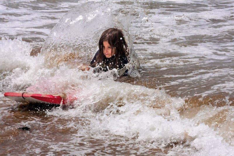 La bambina cad da dalla rottura Wave dell'acqua bassa del bordo di boogie fotografie stock libere da diritti