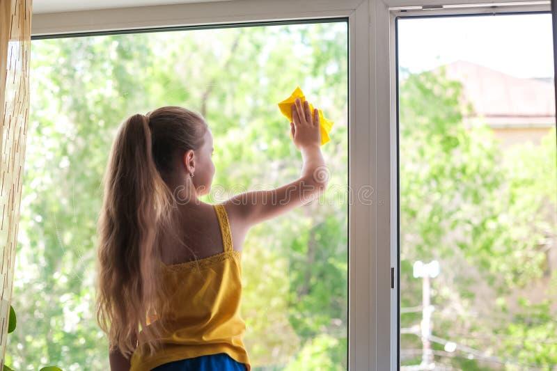 La bambina in camicia e negli shorts blu lava le finestre a casa Figlia con un lavaggio del gatto la finestra immagini stock