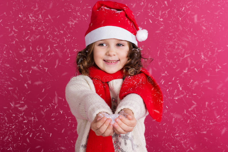 La bambina in cappello di Santa sta tenendo la neve falsa fotografia stock