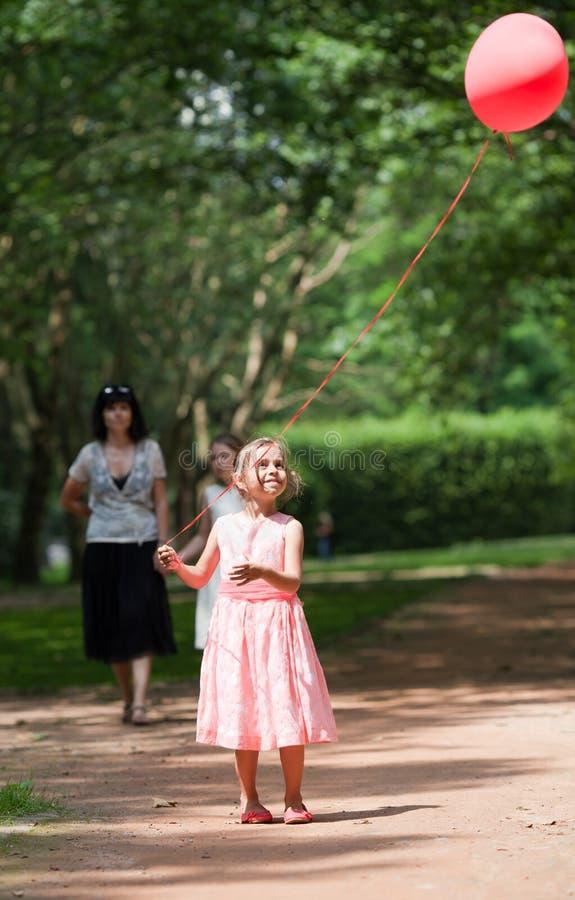 La bambina cerca il pallone tenuto in alto fotografia stock