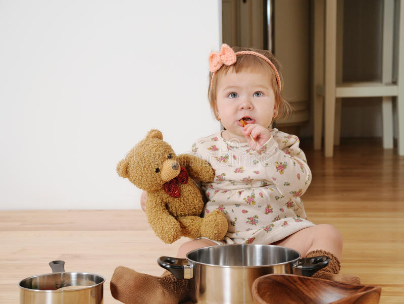 La bambina che cucina con l'orsacchiotto riguarda il pavimento fotografia stock libera da diritti