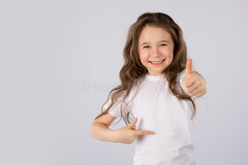 La bambina che mostra i pollici aumenta il gesto in una maglietta bianca su fondo bianco immagini stock