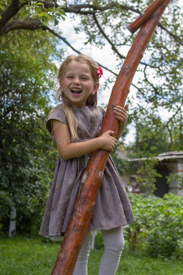 La bambina che ride abbracciando un albero, bella ragazza bionda abbraccia un albero e sorridere fotografia stock libera da diritti