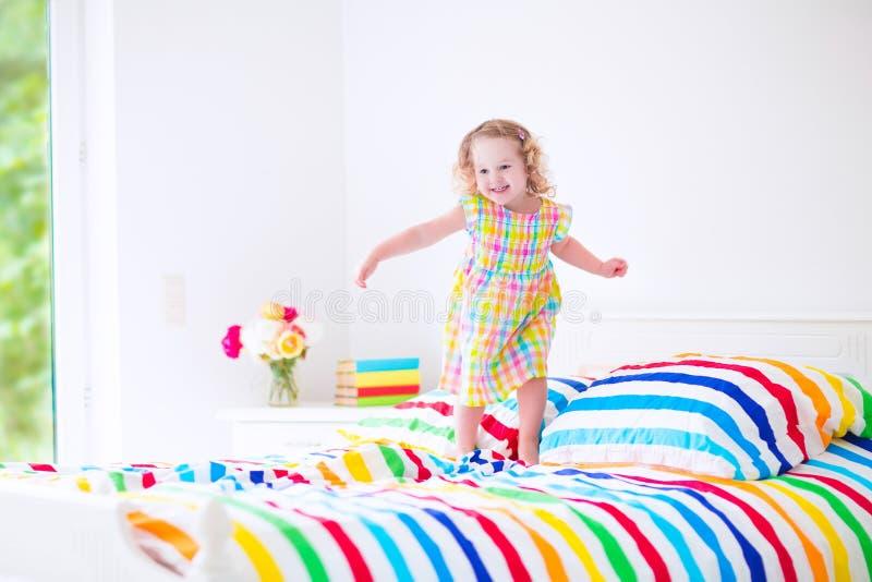 La bambina che salta su una base immagine stock libera da diritti