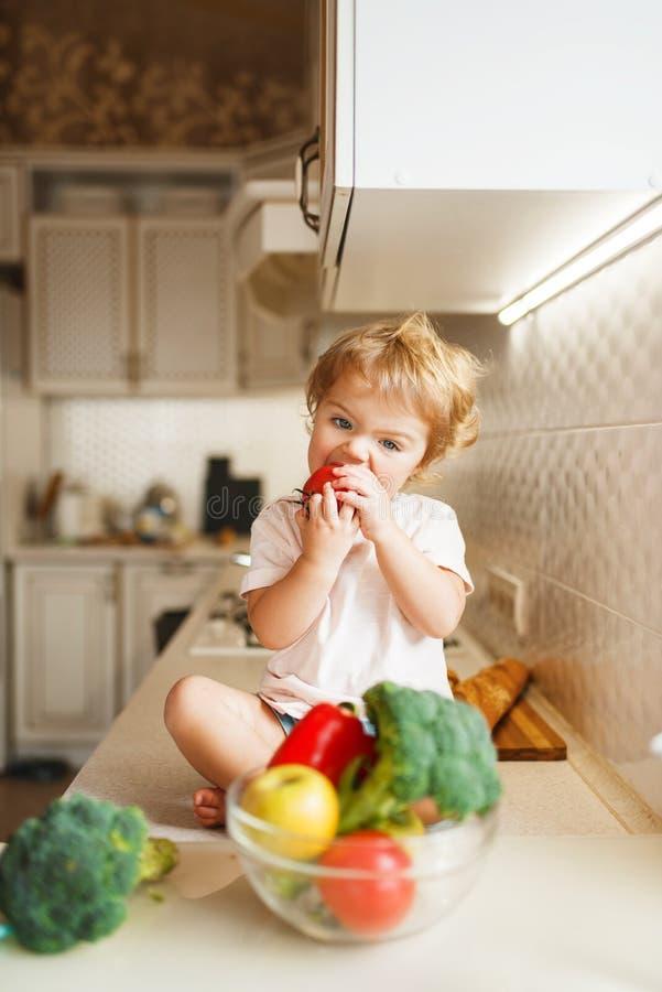 La bambina che si siede sulla tavola e mangia il pomodoro fotografia stock libera da diritti