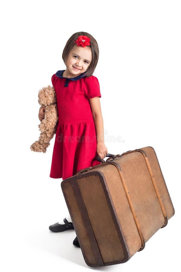 La bambina che sorridono in vestito rosso con la valigia ed il giocattolo sopportano immagini stock libere da diritti