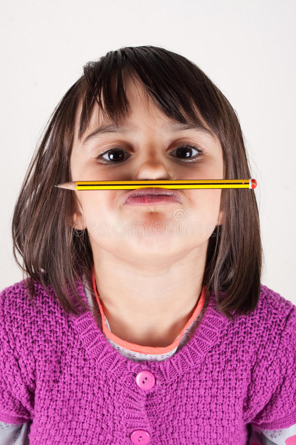 La bambina che tiene una matita gradisce i baffi. fotografia stock