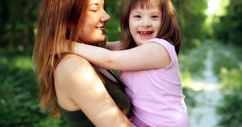 La bambina con i bisogni speciali gode di di spendere il tempo con la madre fotografie stock