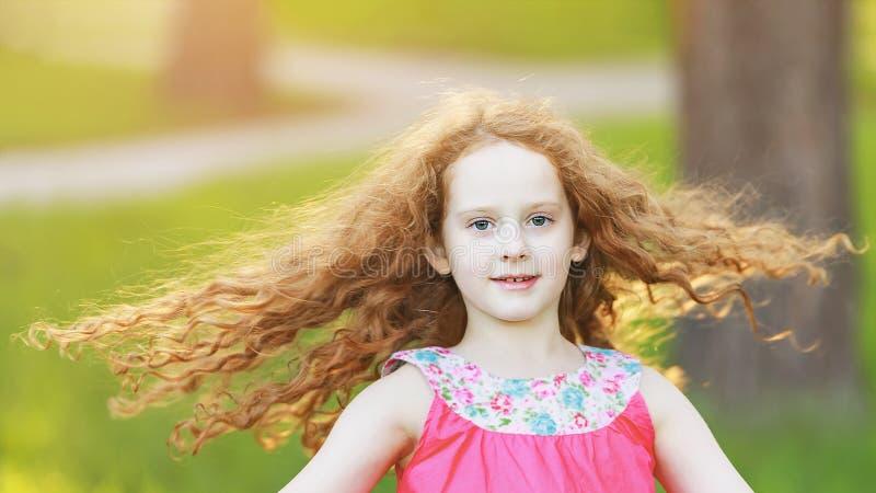 la bambina con i capelli di un volo sta ballando nel parco immagine stock