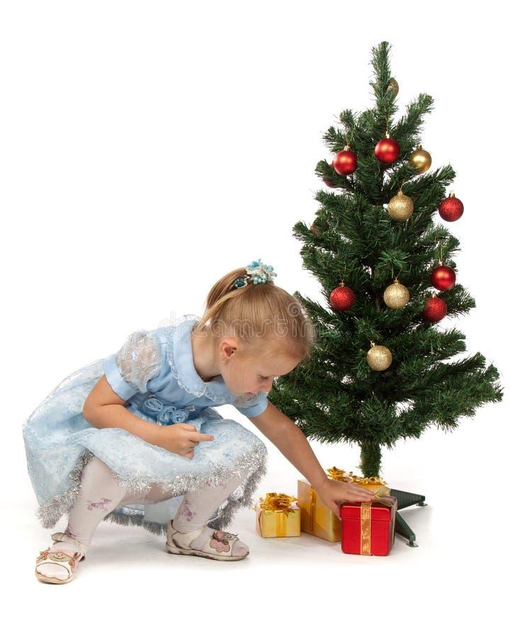 La bambina con i regali si avvicina ad un albero di Natale immagini stock libere da diritti