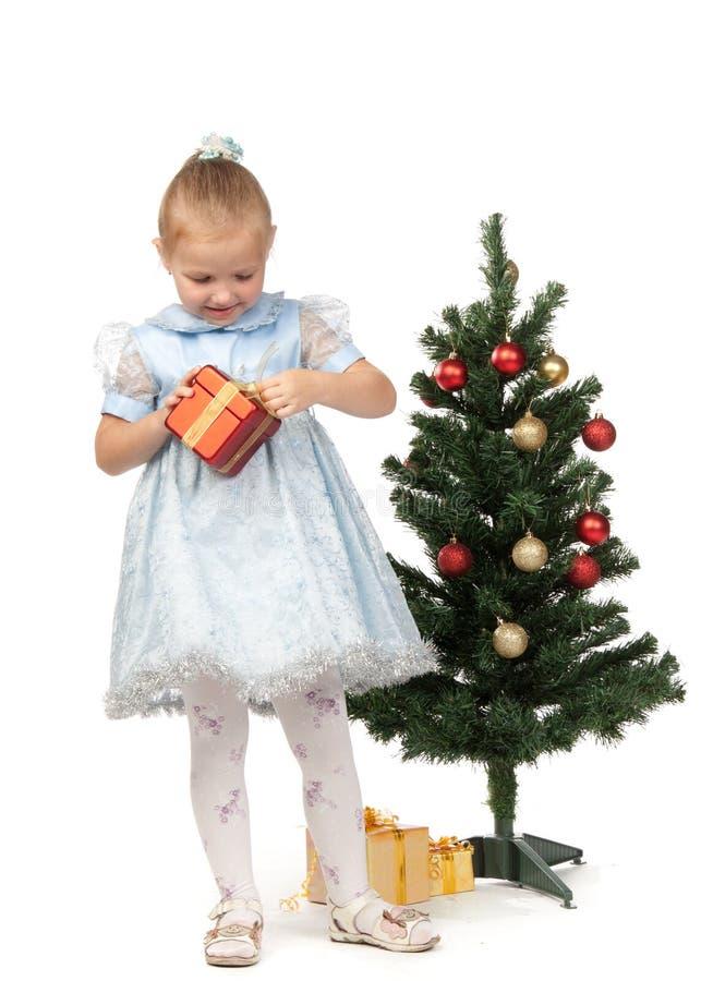 La bambina con i regali si avvicina ad un albero di Natale fotografia stock libera da diritti