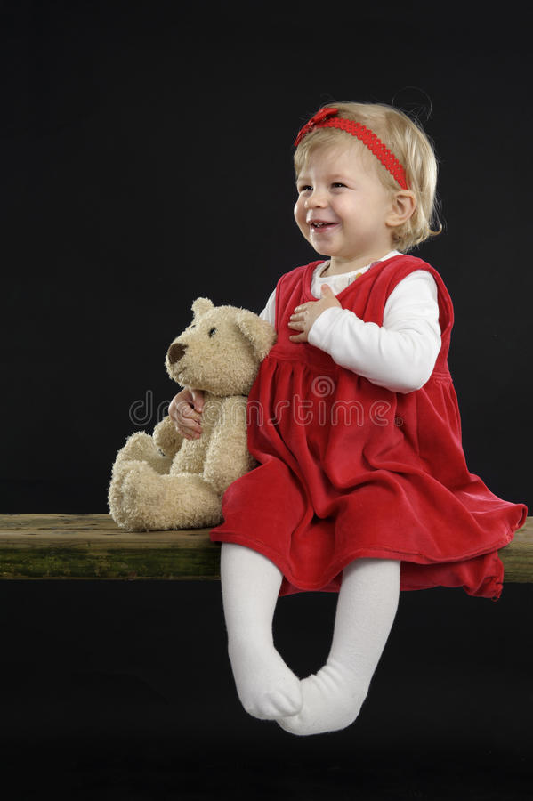 La bambina con il cappello di natale e l'orsacchiotto riguardano il nero fotografia stock libera da diritti