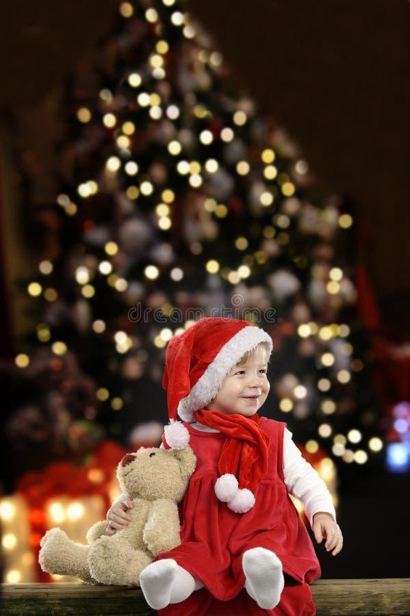 La bambina con il cappello di natale e l'orsacchiotto riguardano il nero immagine stock libera da diritti