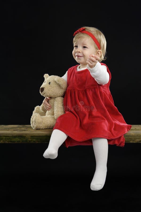 La bambina con il cappello di natale e l'orsacchiotto riguardano il nero immagini stock libere da diritti