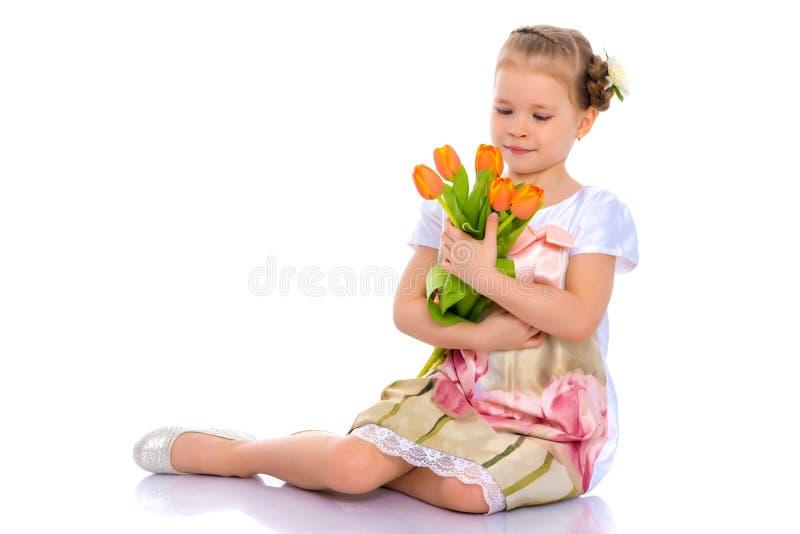 La bambina con il mazzo dei fiori si siede sul pavimento fotografia stock libera da diritti