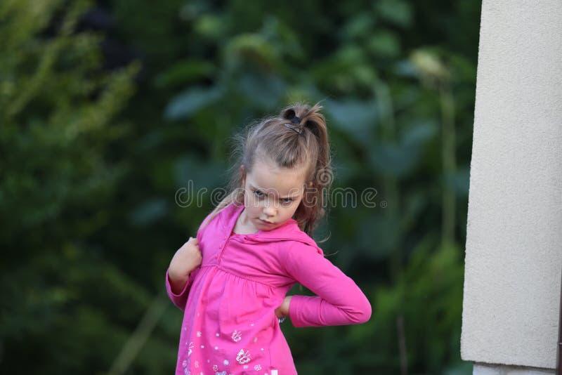 La bambina con la coda di cavallino si è vestita in camicia rosa che fa il fronte arrabbiato fotografie stock