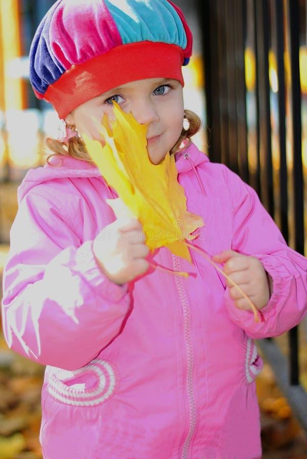 La bambina con un opuscolo giallo fotografia stock