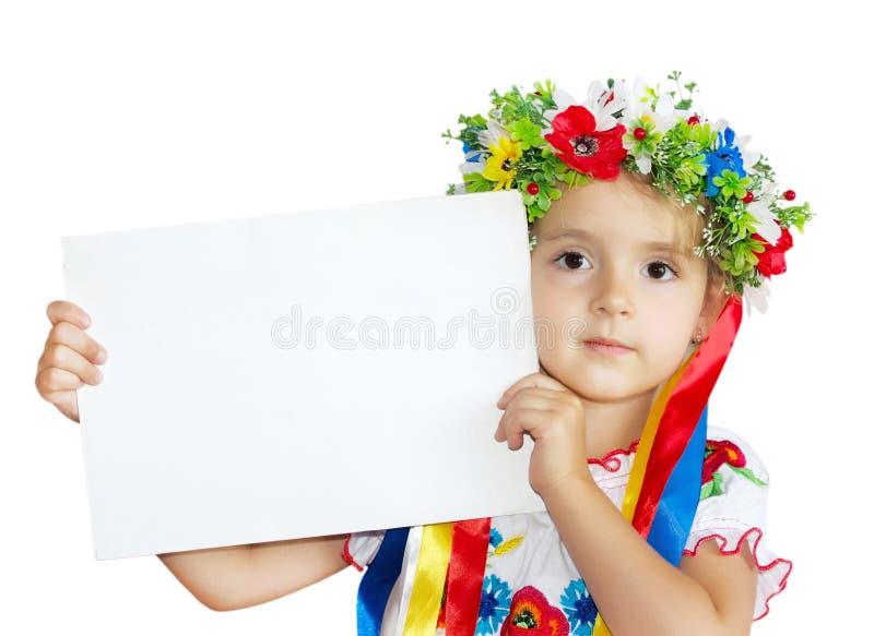 La bambina in costume ucraino tradizionale copre la pappa della tenuta fotografia stock