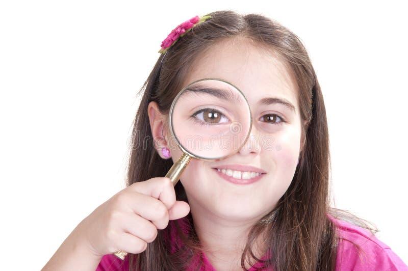 La bambina curiosa sta guardando tramite la lente d'ingrandimento immagini stock libere da diritti