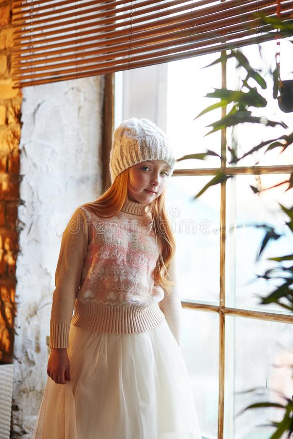 La bambina dai capelli rossi intelligente in un cappello bianco ed in un bello vestito sta sedendosi in un caffè di autunno Ragaz fotografie stock libere da diritti