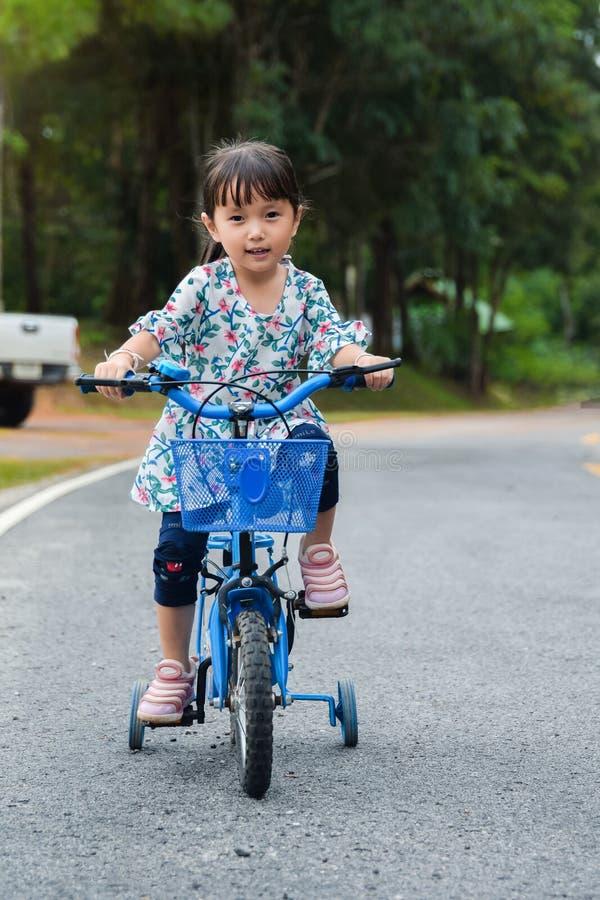 La bambina dei bambini è bici di giro sulla strada immagini stock