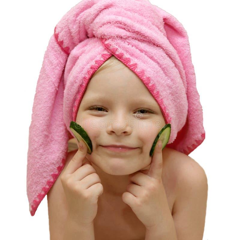 La bambina del bambino fa una maschera di protezione dei capelli del cetriolo in un asciugamano immagini stock libere da diritti