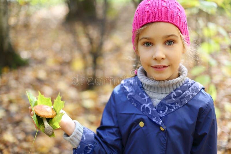 La bambina di sorriso tiene la foglia di acero immagini stock