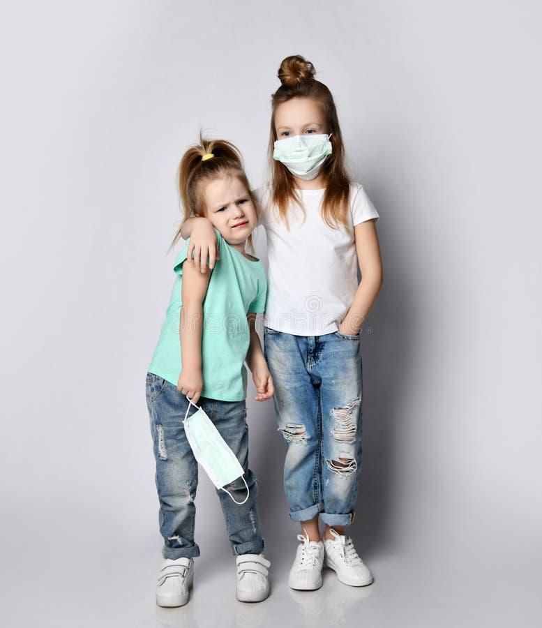 La bambina di una sorella maggiore in maschere mediche del Covid-19 sta con la sua sorellina che recita in modo disubbidiente sen immagine stock