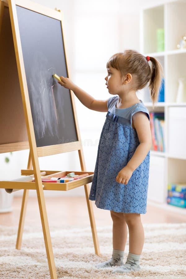 La bambina disegna con gesso sulla lavagna fotografia stock libera da diritti