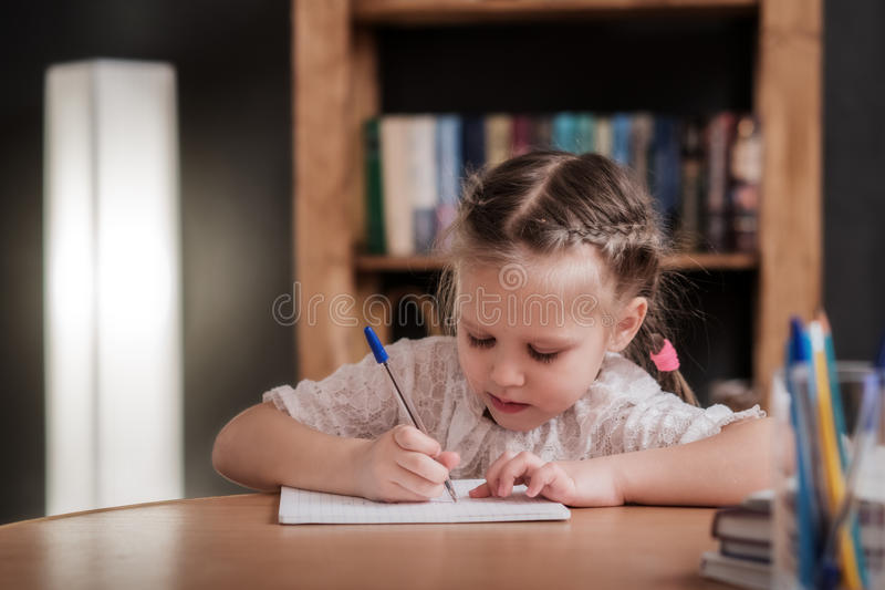 La bambina disegna, impara scrivere immagini stock