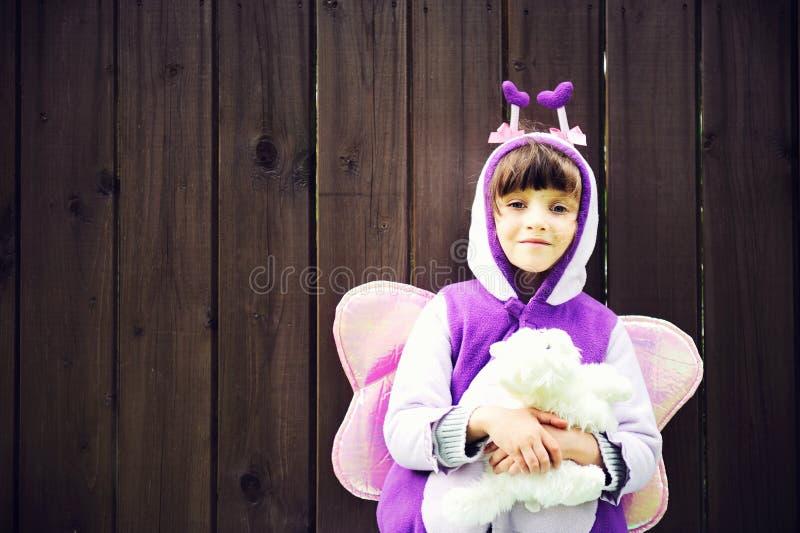 La bambina divertente si è vestita in un vestito della farfalla immagine stock