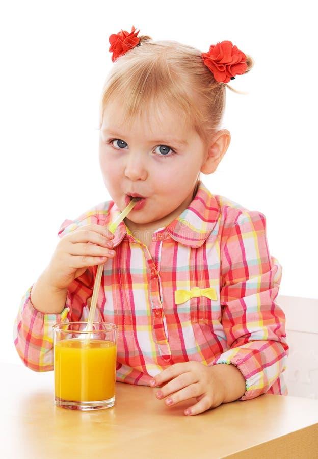La bambina divertente sta bevendo il succo d'arancia da parte a parte immagine stock