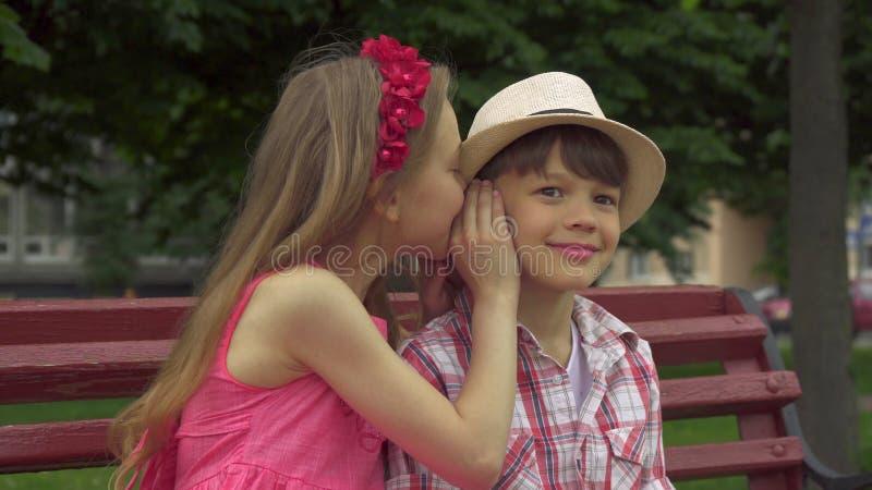 La bambina divide i segreti con il ragazzo sul banco immagine stock libera da diritti