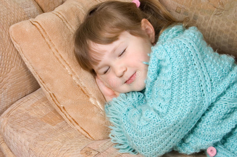 La bambina dorme su un sofà fotografia stock