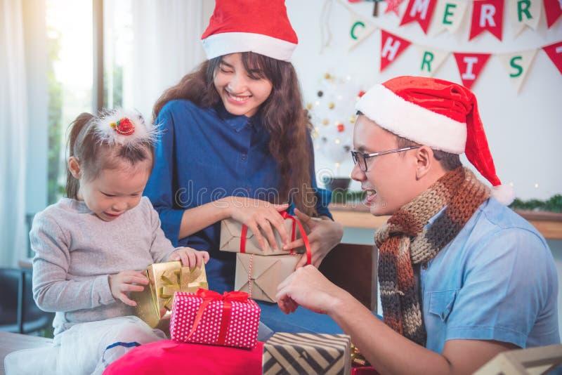 La bambina ed i suoi genitori aprono i contenitori di regalo di natale fotografie stock