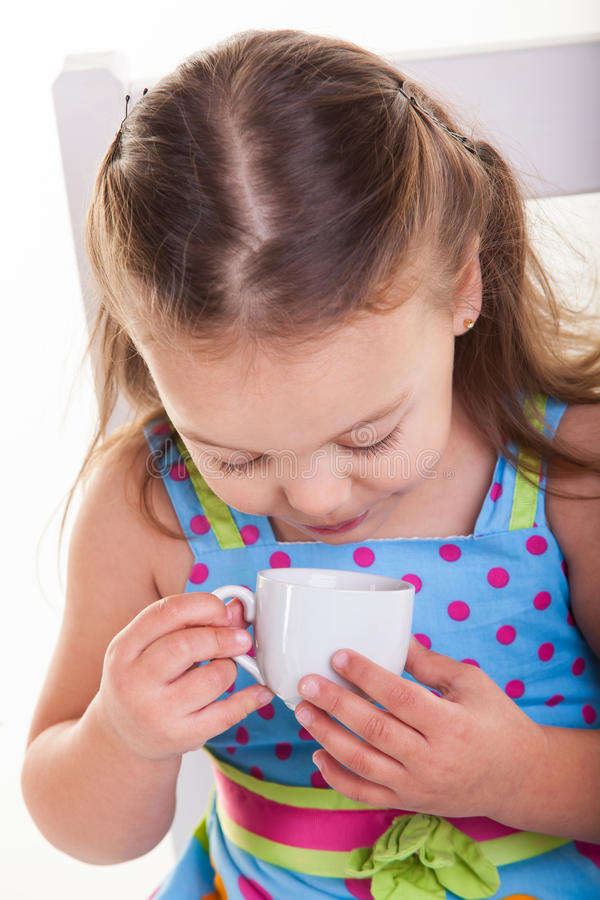 La bambina esamina la tazza. fotografia stock