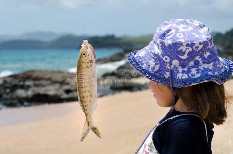 La bambina esamina un pesce su un gancio fotografie stock