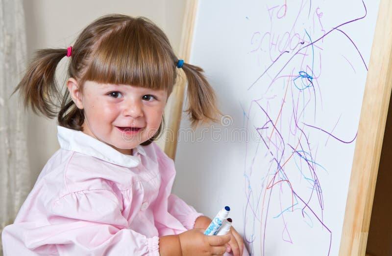 La bambina estrae le pitture immagine stock