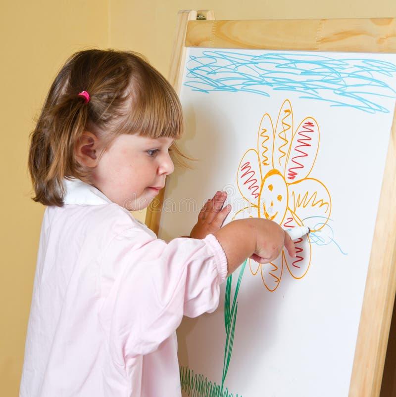 La bambina estrae le vernici immagine stock