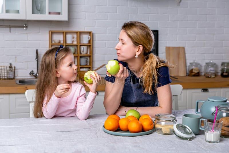 La bambina felice e la sua bella giovane madre hanno insieme prima colazione in una cucina bianca Sono divertentesi e mangianti l fotografia stock