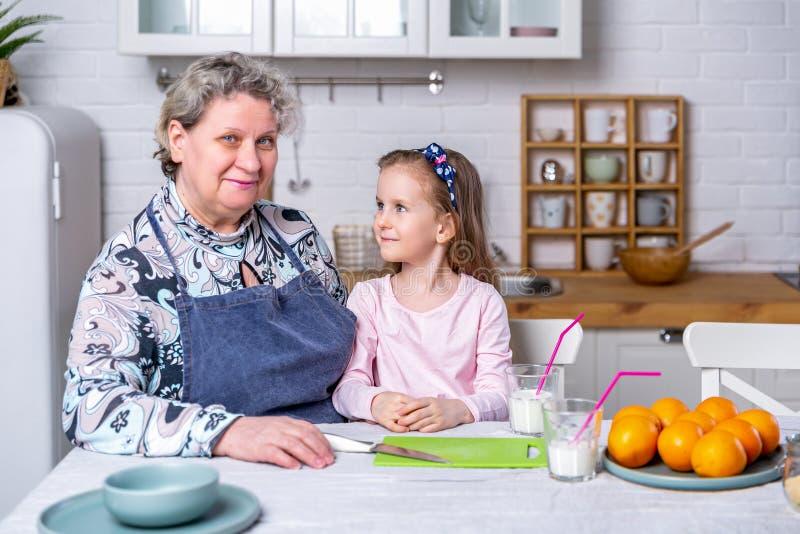 La bambina felice e sua nonna hanno insieme prima colazione in una cucina bianca Sono divertentesi e giocanti con i frutti fotografie stock