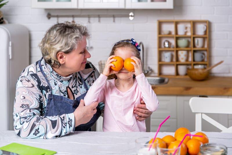 La bambina felice e sua nonna hanno insieme prima colazione in una cucina bianca Sono divertentesi e giocanti con i frutti immagine stock