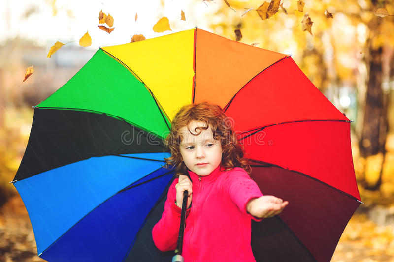 La bambina felice getta le foglie di autunno nell'aria fotografie stock