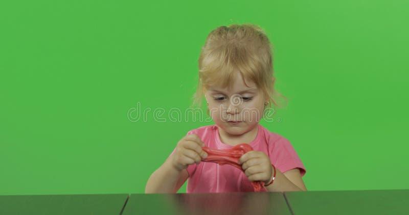 La bambina felice gioca con plasticine sul fondo chiave dell'intensità fotografie stock libere da diritti