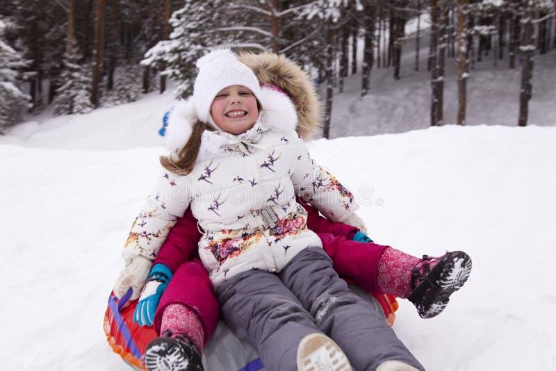 La bambina felice grida con delizia, rotolante con la collina della neve fotografia stock