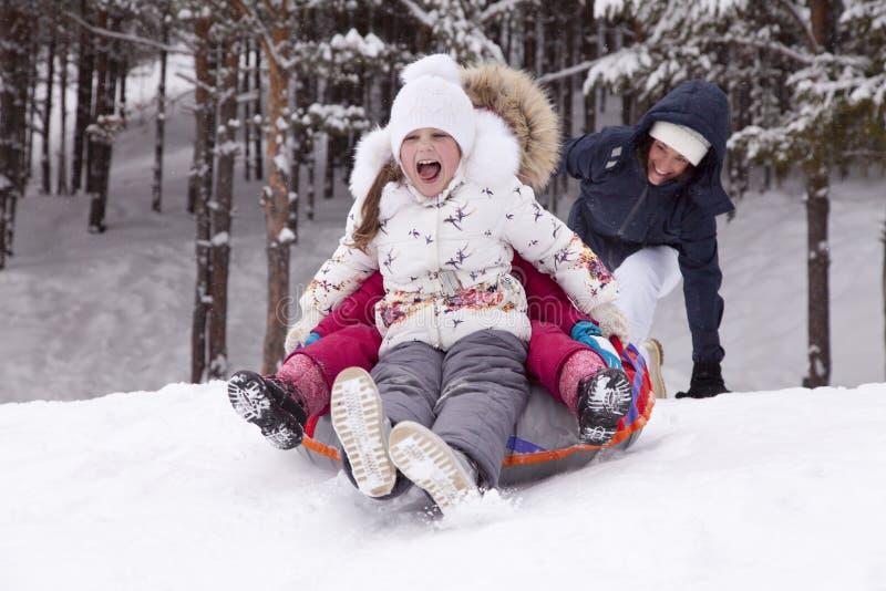 La bambina felice grida con delizia, rotolante con la collina della neve immagine stock