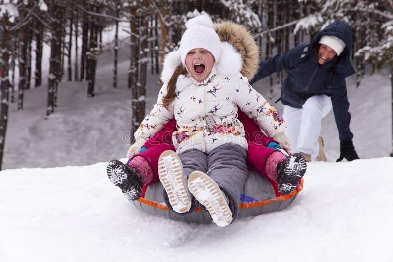 La bambina felice grida con delizia, rotolante con la collina della neve fotografie stock libere da diritti