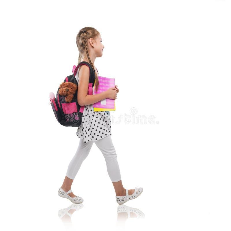 La bambina felice inizia la scuola, isolata immagini stock